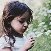 girl looking at dandelion flower
