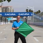 Aaron Likens in blue shirt and black pants holding green flag on the Long Beach Grand Prix Course