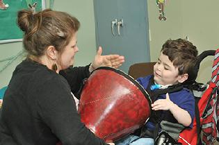 Woman holding a red drum while a boy in a wheelchair plays