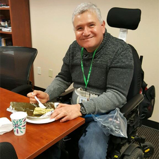Program participant Jorge C smiles while enjoying a meal in his powered wheelchair at our office.