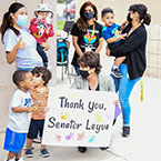 Senator Leyva holds a thank you sign while surrounded by kids and moms
