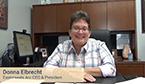 Donna Elbrecht seated at her desk