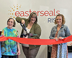 A woman cuts a large ribbon held by two others