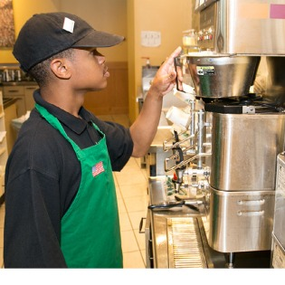 Young man working as barista