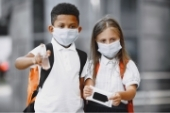 two children wearing masks and holding hand sanitizer
