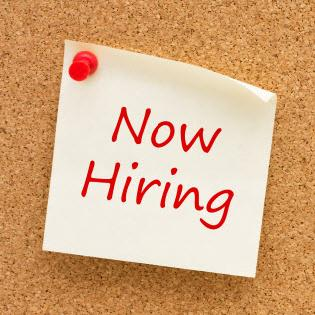 Now Hiring note on cork board