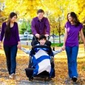family walking with disabled child in autumn