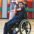Matteo, accessible martial arts student, participates in a stretch during class while sitting in his wheelchair