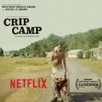 A man in a wheelchair is pushed by his friend down a long path. Crip Camp is written across it