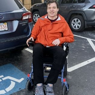 Dan sitting in his new power wheelchair and smiling.