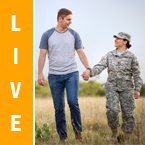 Live. Photo of a female army member and her husband holding hands in a field.