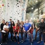 A group of male & female Veterans stand & smile together in front of a rock-wall, all wearing rock-climbing gear, for a Veterans Peer Group outing.
