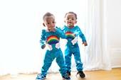 twin toddlers in rainbow onesies