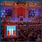 a large audience watches a military band perform in a large music hall with stars and stripes decorating the walls.