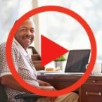 Man at desk, play button over him