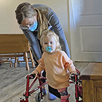 Everleigh walking with her walker and Easterseals therapist