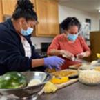 Two women preparing food in a kitchen wearing masks