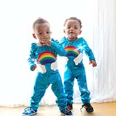 twin toddlers in rainbow onesies