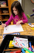 girl painting on paper with art kit on table