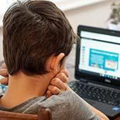 kindergarten aged boy sitting in front of computer