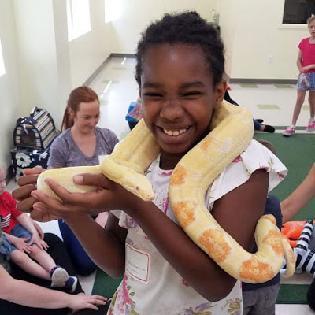 Child holds snake during respite program petting zoo