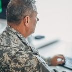 A veteran wearing camouflage military uniform sits facing a computer, using the keyboard
