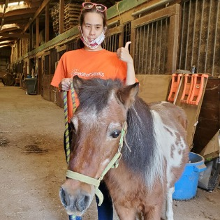 Young woman with horse in stable