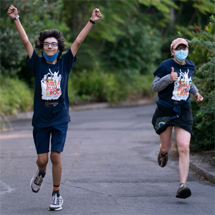 2 young teens running our 5k course at the Oregon Zoo. One of them has their arms in the air, trimphantly, and the other is giving a