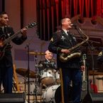 a man wearing a national guard uniform plays the saxophone and sings onstage