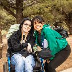 A woman in a wheelchair poses with another woman bending down next to her in front of a tree at camp.