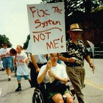 Woman in a wheelchair at a protest with a sign