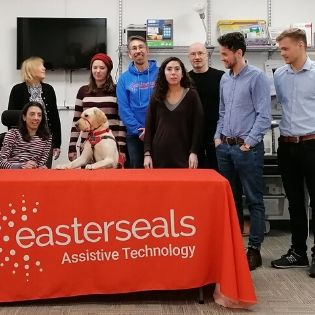 ESMA employees smiling with the Present Pal team & service dog behind a table.