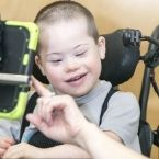 a young child with a disability smiles while using assistive tech